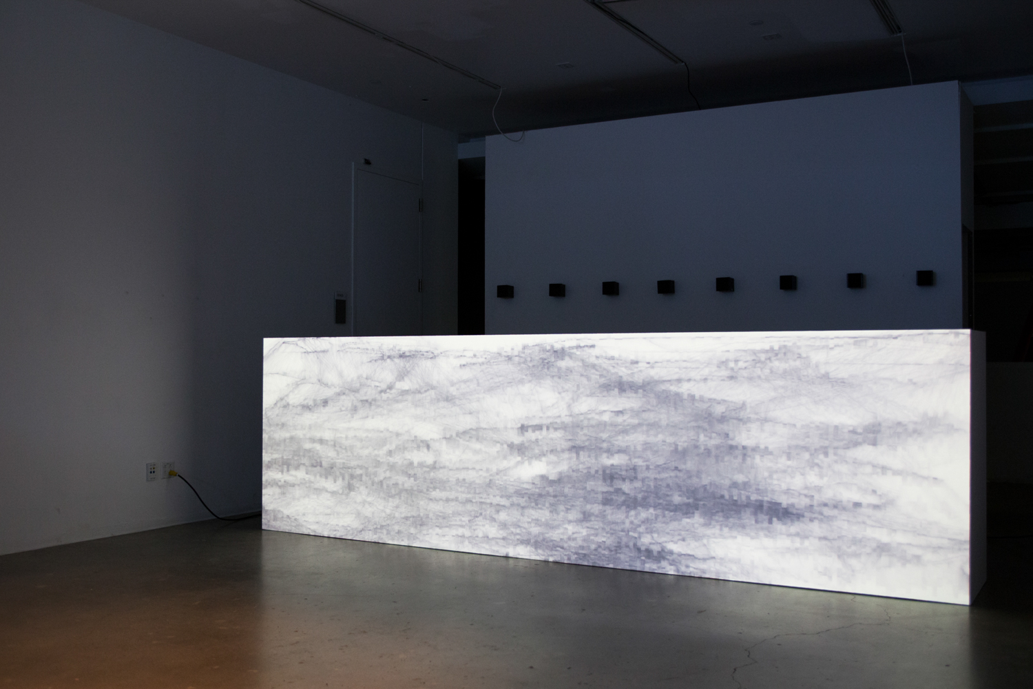 Generative audiovisual landscapes being projected on a low wall of the EDA solo show gallery.