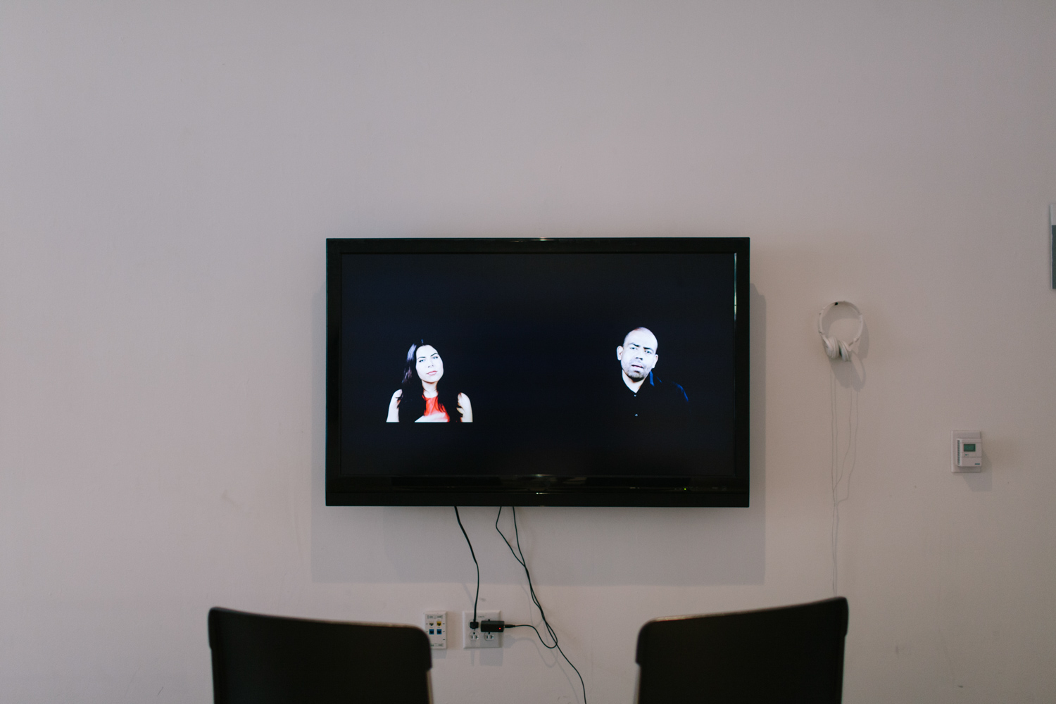 Two chairs in front of a television monitor.