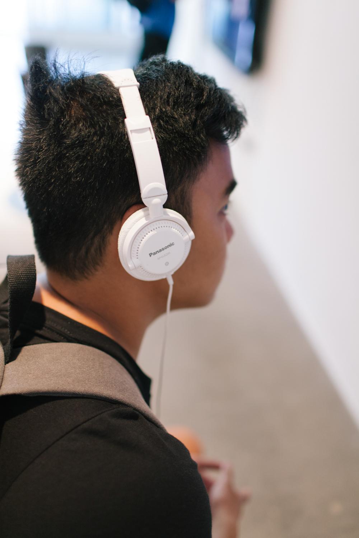 Person wearing white Panasonic headphones.