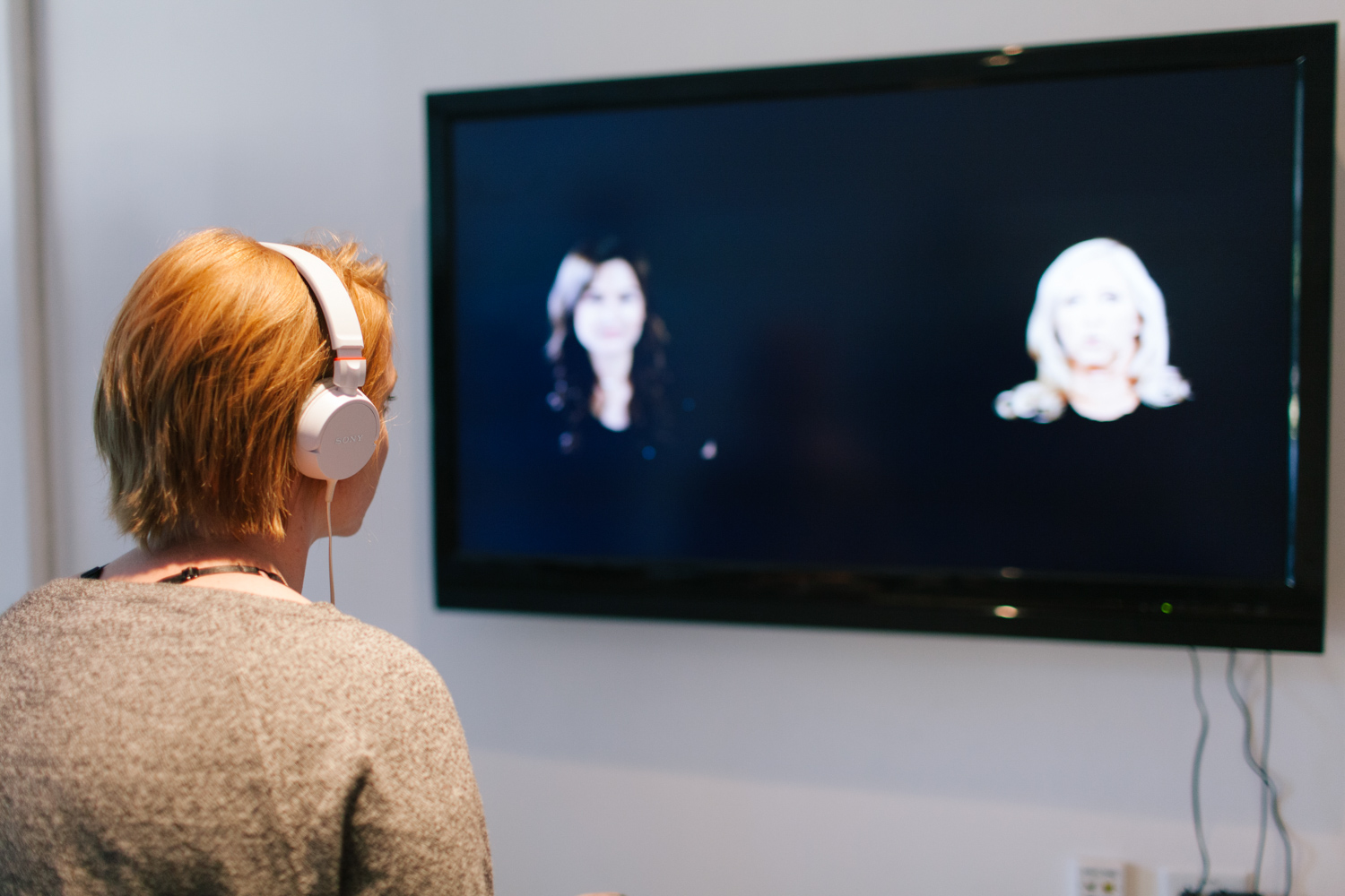 Person wearing hedaphones in front of two people being displayed on a tv monitor.