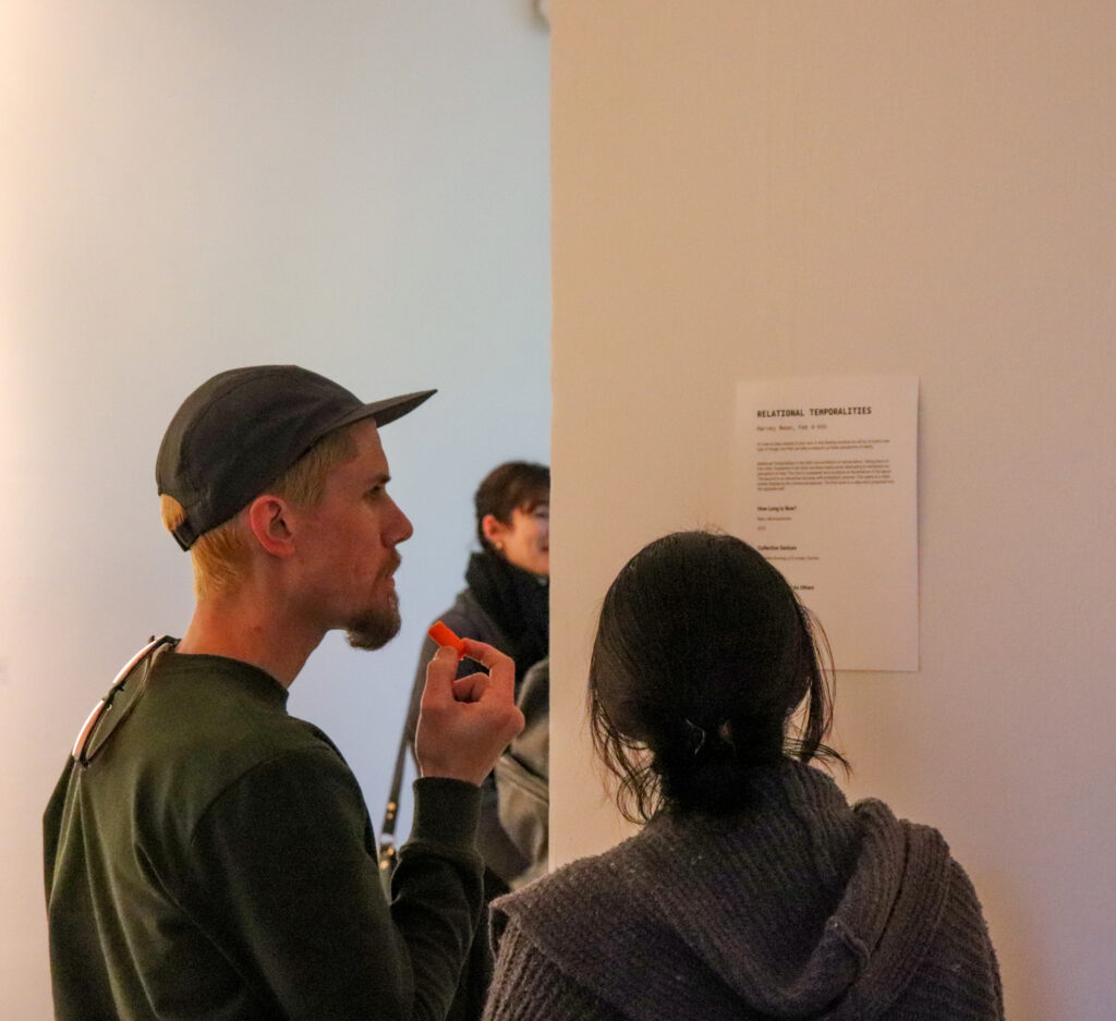 Gallery visitors look at the press release of Harvey Moon's Relational Temporalities mounted on the wall of the gallery.
