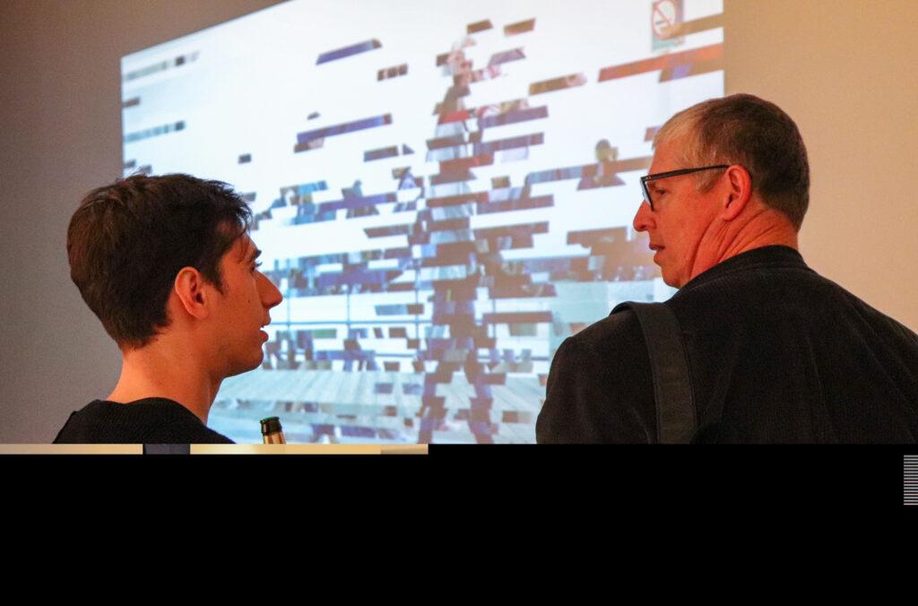 Harvey Moon talks to Peter Lunenfeld in front of Harvey's projection work.