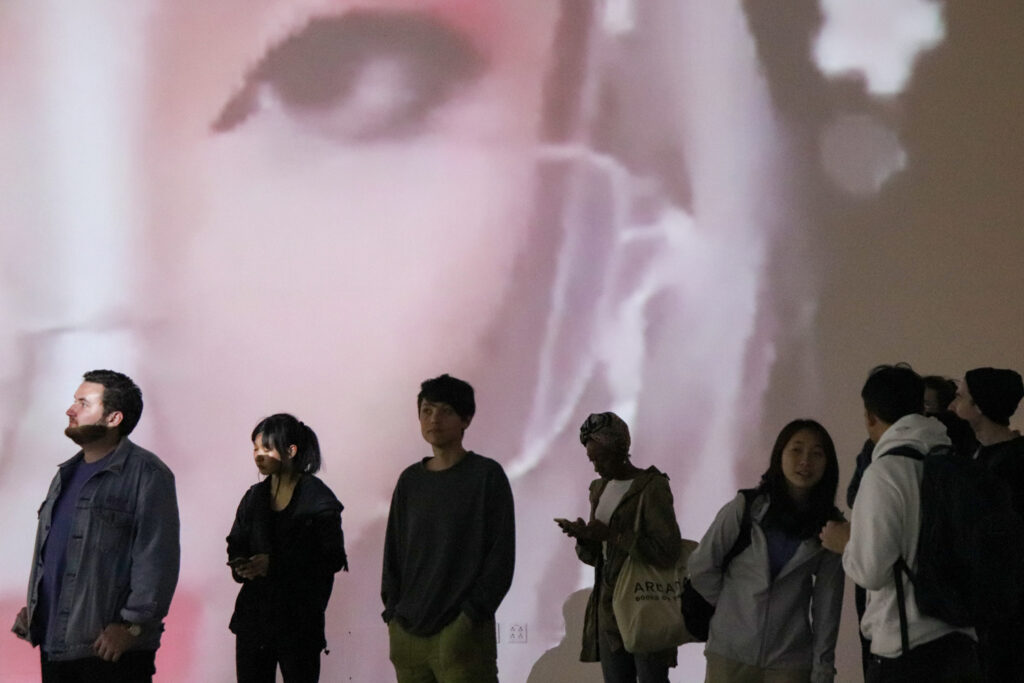 People standing in front of Zheng Fang's projection work in the EDA pit. The projection is of a twitch streamer's eye.
