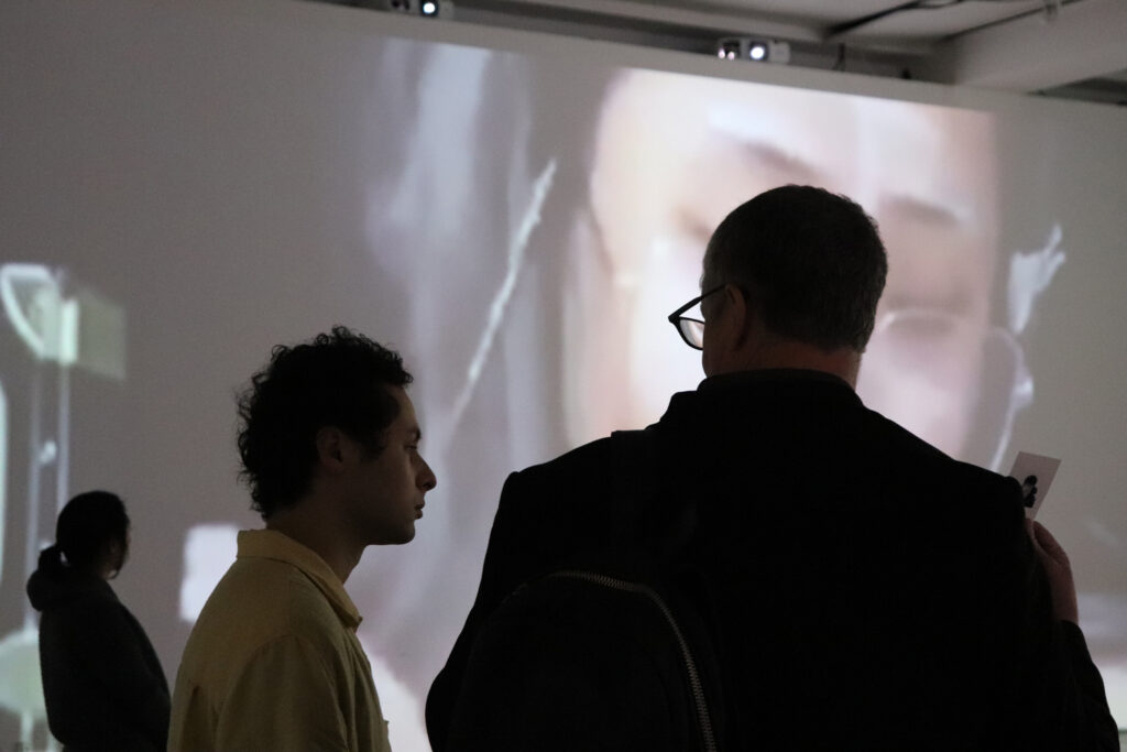 People talking in front of Zheng Fang's projection work.