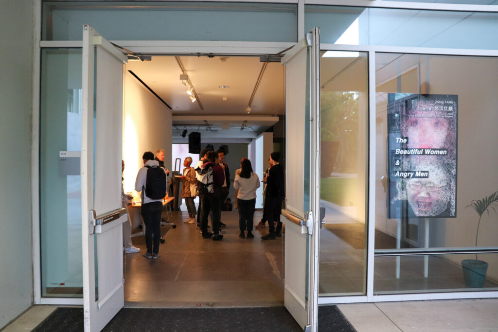 People socializing and eating at the opening of Zheng Fang's exhibition.