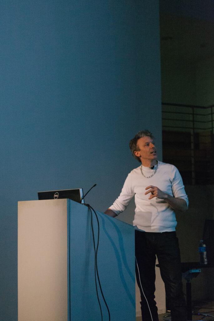 Person speaking at a pedestal during Daniel Landau's lecture.