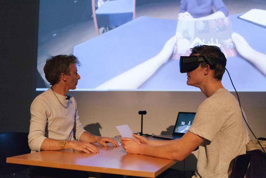 Person is wearing a VR headset and holding their hands out to another person on a desk.
