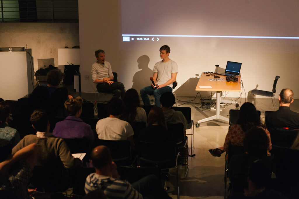 Daniel Landau's lecture in the EDA pit. Two people are lit sitting in chairs in front of the EDA pit center wall.